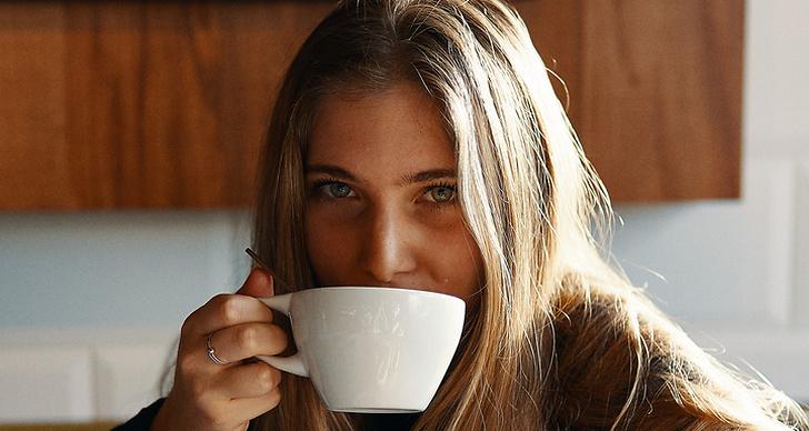 En tjej som dricker ur en stor kopp