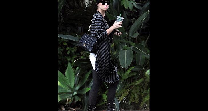 Katy Perry kombinerar väskan med nitprydda boots och take away-kaffe.