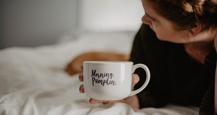 Kvinna ligger i en säng och håller i en kaffekopp