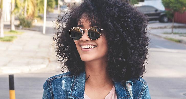 Tjej med lockigt hår och solglasögon ler