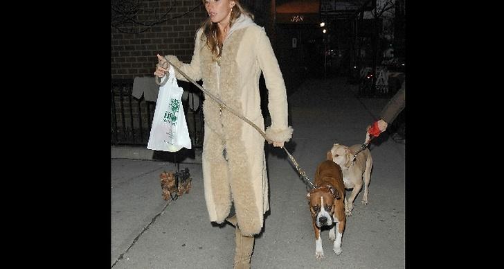 Gisele på hundpromenad i beige, hellång kappa.