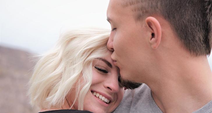 En kille pussar en tjej på pannan som lutar sig mot honom och ler.