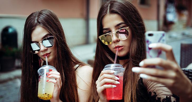 Två tjejer poserar med varsina juicer när de tar en selfie till Instagram.