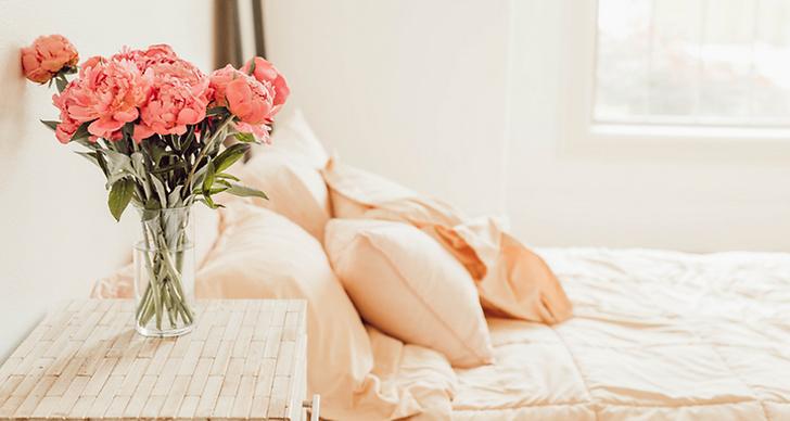 Säng med ett bord som det står en vas med blommor på