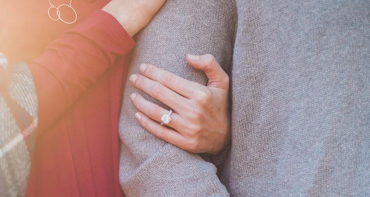 Hand med ring som hållet om en arm